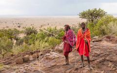 two masai warriors dressed in red and pinks in a desert landscape