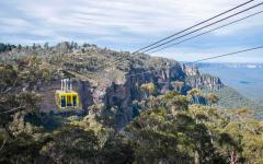 yellow cable car crosses the blue mountain range in new south wales