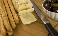pepper jack cheese breadsticks and olives on a chopping board