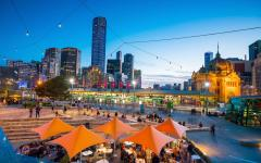 melbourne city buildings lit up in the evening and with diners outside eating and drinking