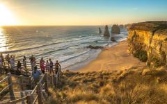 people on a viewing platform looking out to the twelve apostles along great ocean road at sunset