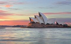 sydney opera house at sunrise surrounded by calm water