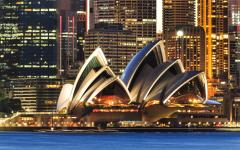australia sydney opera house at night with high rise buildings lit up