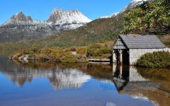 view of a hut on the shore of water with cradle mountain in tasmania