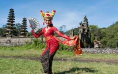 Balinese woman performs dance in traditional dress.