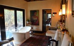 Refined bathroom with traditional artwork on the walls in the Royal Malewane | South Africa