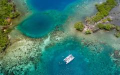 An aerial image of a catamaran anchored by a tropical coral reef in Belize