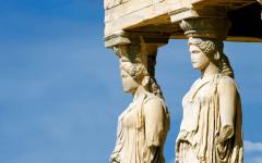 two statues at the acropolis greece against a blue sky