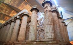 Ancient Greek stone columns being restored under a large canopy at the Apollo Temple in Bassae, Greece