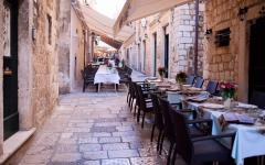 Restaurant tables on an old street in Dubrovnik, Croatia.
