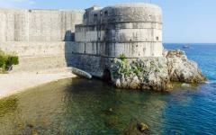 Summer fortress view, Lovrijenac tower on rock and clear water of Adriatic Sea
