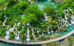 An aerial shot of a wooden walkway through Plitvice lakes and waterfalls in Croatia.