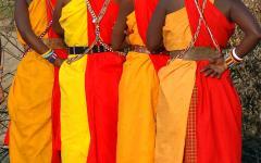 masai women in colorful garments prepare for a traditional dance