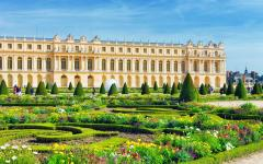 the lush green garden and building of versailles