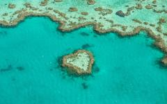 a love heart shaped island surrounded by turquoise water forms part of the the great barrier reef