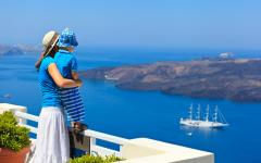 Mother and her son in Greece watching boats sail by on the Aegean Sea