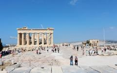 Groups of tourists exploring the Acropolis of Athens with the Partheon and the Erechtheum temples in view
