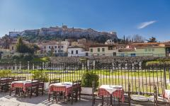 An outside restaurant dining area with a view of Acropolis Hill in Athens, Greece