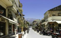 Street view of pedestrians and parked vehicles in Chania, Crete, Greece