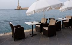 An outside cafe on the beach of Chania Harbor with the Lighthouse of Chania standing tall in the background