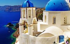 The famous blue-dome Santorini Church with the Aegean Sea in the background