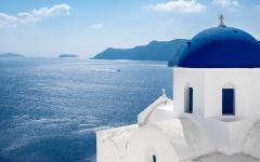 white greek church with blue dome faces blue sea on a bright sunny day