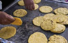Handmade yellow corn tortillas on the comal or hot iron