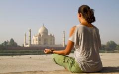A woman practicing yoga in front of the Taj Mahal in Agra India