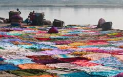 People washing colorful garments on the sandy banks of the Yamuna River in Agra India