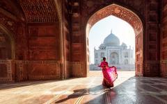 Woman in red sari admiring the Taj Mahal in Agra India