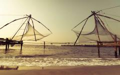 The sun begins to set over fishing nets in Cochin.