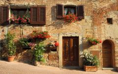 House with vibrant flowers hanging on its wall in Tuscany.