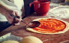 A chef ladles on fresh tomato sauce onto a pizza base.