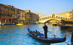 A gondola transports tourists on a Venice canal, Italy.