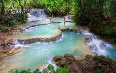 pristine waterfalls in laos surround by lush green trees