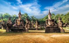 buddhist statues with trees and cloudy blue sky