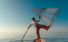 fishman holds a net and balances with one leg on the end of a boat