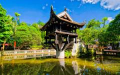 one pillar pagoda standing in water surround by green trees and a blue sky