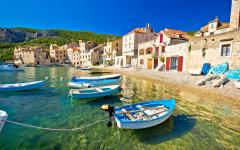 Boats tied up in shallow water in Komiza village on the island of Vis in Croatia.