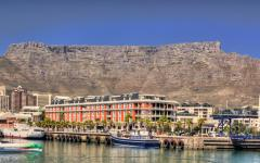 View of a Cape Town waterfront in South Africa with boats on the water and hotels in the background