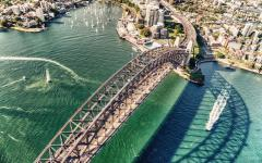 overhead view of the sydney harbor bridge with boats on the water