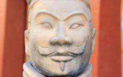 a terracotta army figure against a red background