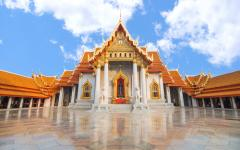 orange roofed temple with white pillars and a blue cloudy sky