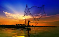 fisherman throws fishing net into river at sunset