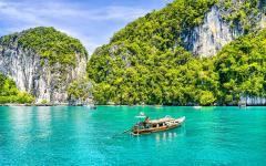 small boat floats on beautiful green water with cliffs