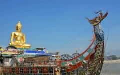 golden buddha statue sits on top of a colored metal boat with a dragon at the front