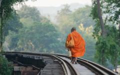 Monks walking along the railway along the Noi River.