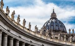 statues and a dome make up the skyline at vatican city