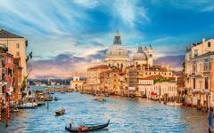 Beautiful view of traditional Gondola on famous Canal Grande with Basilica di Santa Maria della Salute, Venice.
