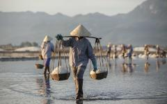 Farmers carrying salt in Vietnam.
